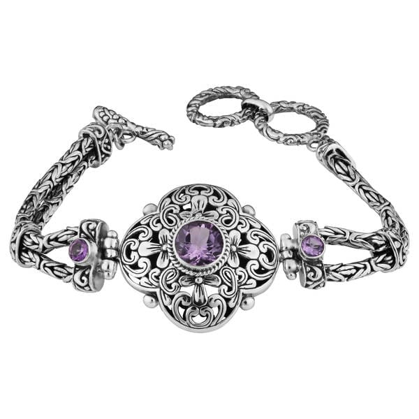 You'll be raking in the compliments with this handcrafted silver bracelet. Featuring genuine amethyst stones, this beautiful piece was designed and made by Indonesian artisans. Fastened with a toggle closure, this 'Cawi' bracelet is sure to turn heads.     Product Features:    Story Behind the Art:   From Bali, Indonesia comes a talented Artisan named Kadek Hendra who believes that handcrafted art is all about bringing back to fashion some of the most traditional and interesting designs of the various Indonesian cultures with the right contemporary hues and designs. Kadek comes from a family of silversmiths, his grandfather was one of the first in Celuk followed by his father and he is the third generation. Kadek gives soul and great character to each and every piece he designs.     What is Worldstock?      The handcrafted nature of this product will produce minor differences in design and sizing. Subtle variations will occur from piece to piece, adding to its unique qualities. Measurements and weights may vary slightly. Treatment code E. See    Gemstone Treatments    for further information.      Imported      Ships Carbon Neutral*            Enhance your style with beautifully crafted amethyst 'Cawi' bracelet     Bracelet made of fine .925 sterling silver     Jewelry designed and handcrafted by talented artisans from Indonesia     Bracelet fits wrist sizes from 7 to 8 inches long     Bracelet face measures 38 mm wide by 1.2 inches deep         All measurements are approximate and may vary slightly from the listed dimensions.        T.W. (total weight) is approximate. The weight may vary up to two-tenths of a carat.        Treatment code H (Heating) for main stone. See   Treatment Guide   for all treatment code information.